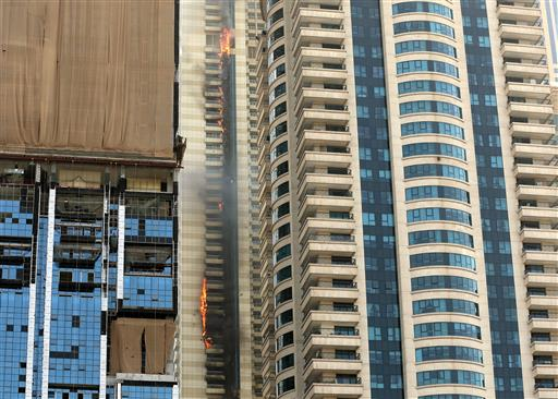 A fire burns at the Sulafa Tower skyscraper in Dubai, United Arab Emirates on July 20, 2016. The residential skyscraper in Dubai caught fire in the densely populated Marina district, sending columns of smoke into the air and pieces of the building's facade tumbling below. It's the latest in a number of skyscraper fires across the United Arab Emirates in recent months. The most prominent was a New Year's inferno at a 63-story residence near the world's tallest tower. (AP Photo/Adam Schreck)