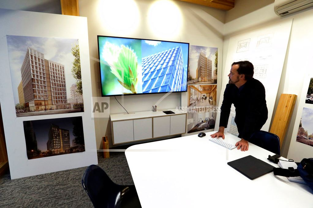 In this Nov. 15, 2016, file photo, Lever Architecture founder Thomas Robinson looks over artist renderings in Portland, Ore., of a 12-story all-wood building that his firm is working on to be built in Portland's trendy Pearl District. City officials in Portland have approved a construction permit for the first all-wood high-rise building in the nation. Developers announcing the approval Tuesday, June 6, 2017, say it's a milestone for wood technology. (AP Photo/Don Ryan, File)
