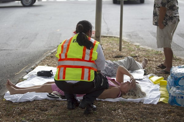 A paramedic checks on a woman, lying on a median, after she and others exited the Marco Polo apartment complex as firefighters continue to battle a blaze at the high-rise, Friday, July 14, 2017, in Honolulu. (AP Photo/Marco Garcia)